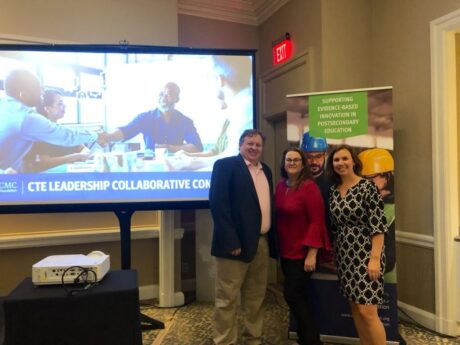 """James Bartlett, Michelle Bartlett, and Jordan Dolfi stand in front of a projection screen that features an image of 4 people around a conference table shaking hands, and the words """"CTE Leadership Collaborative Convening"""". A poster is behind them that is partially blocked, but the words """"Supporting evidence-based innovation in postsecondary education"""" is visible."""